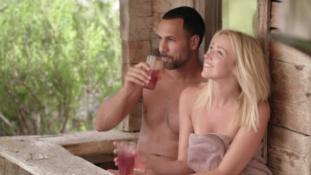 original wooden outdoor sauna hut - sporty man and woman with long blonde hair couple in their 30s wearing towels only, he sits already in front of the shack while she is exiting the hot sauna, sitting down and drinking out of plastic cups – paning camera - halbbekleidet stock-videos und b-roll-filmmaterial