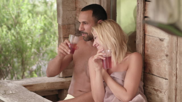 original wooden outdoor sauna hut - sporty man with dark short hair and woman with long blonde hair, couple in their 30s wearing towels only, leaving the sauna and sitting down in front of the shack refreshing drinking with healthy beverage in cups - タオルにくるまる点の映像素材/bロール