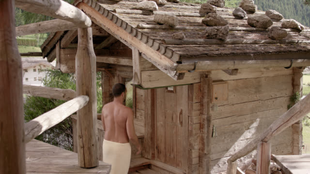 original wooden outdoor sauna hut with rocks on the roof on a sunny day – tanned man in his 30s with short dark hair wearing a towel only walking down steps, opening the wooden door, entering the sauna shack and closing the entrance – camera tilts up - sauna stock videos and b-roll footage