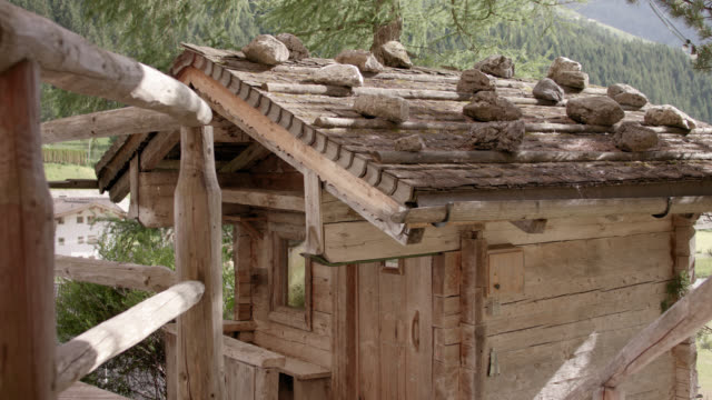 original wooden outdoor sauna hut with rocks on the roof on a sunny day in the austrian alps - locked camera - sauna stock videos and b-roll footage