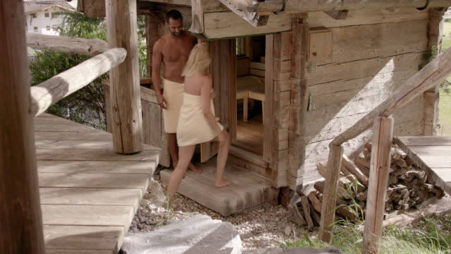 original wooden outdoor sauna hut with rocks on the roof - sporty man and woman couple in their 30s wearing only towels, walking down steps towards the shack, he opens her the door and both entering the hot sauna, he closes the door – camera tilts down - sauna stock videos & royalty-free footage