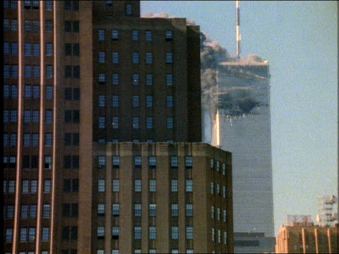 Originally filmed on 35mm / Tower 1 burning Tower 2 obscured by buildings / smoke at upper levels of Tower 1 / PAN from 'Collateral Damage' movie...