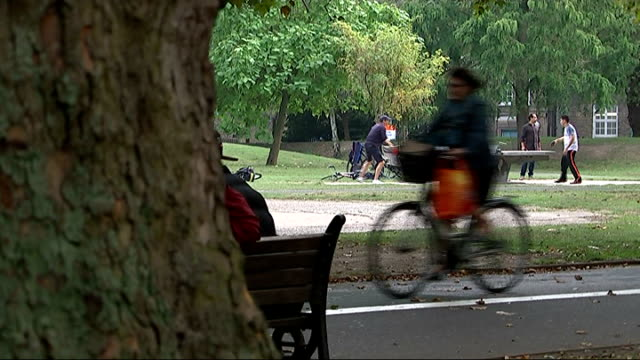 origins of term 'indian summer'; london: cyclist along through park - people playing table tennis in background - indischer subkontinent abstammung stock-videos und b-roll-filmmaterial