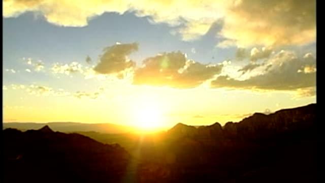 Origins of term 'Indian summer' T13100459 / TX Arizona **McGivern interview overlaid SOT** Back view two people away thru scrub land Sun setting...