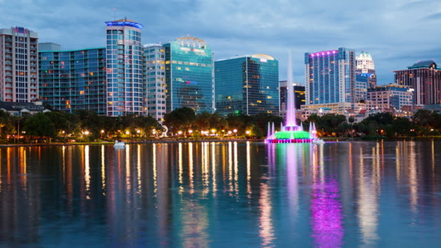 orlando, florida city skyline on lake eola as night falls - time lapse - orlando florida stock videos & royalty-free footage