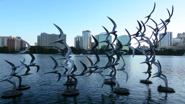 orlando florida lake eola take flight douse blumberg skyline twilight colored lights on statue birds with skyline skyscrapers on water - orlando florida stock videos & royalty-free footage
