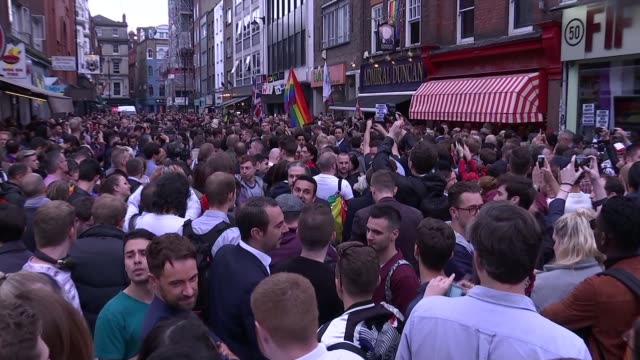 thousands attend vigil in soho england london soho ext crowd of people attending vigil for victims of orlando shootings bunch of red and white roses... - itv london lunchtime news点の映像素材/bロール