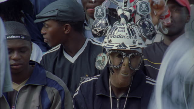 Orlando Pirates fan in decorative hat and oversized glasses, Johannesburg Available in HD.