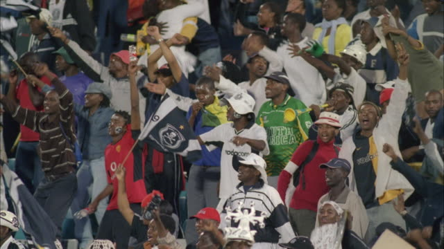Orlando Pirates fans dancing and waving their hands in air, Johannesburg Available in HD.