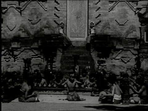 vídeos de stock e filmes b-roll de ornate balinese hindu temple by moonlight with gamelan orchestra amd dancers / people sitting in a circle with kneeling hand dancer in middle / boy... - gamelão