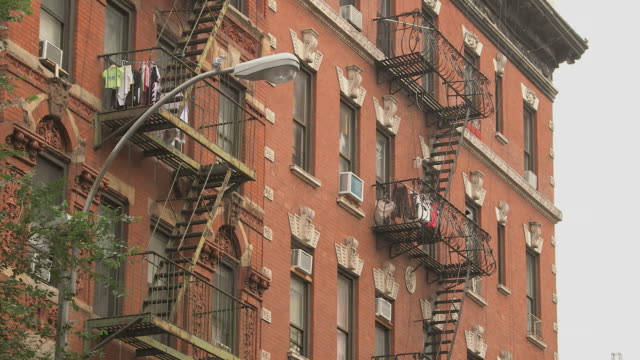MS Ornate brick apartment building with laundry drying on fire escapes / New York, New York, USA