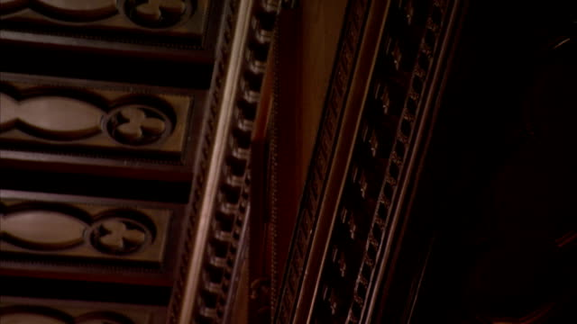 Ornate carvings decorate wood paneling and beams in an art deco former London cinema. Available in HD.