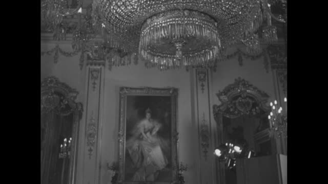 CU ornate chandelier in White Drawing Room of Buckingham Palace tilt down portrait of Queen Alexandra on wall / ornate ceiling of Drawing Room tilt...