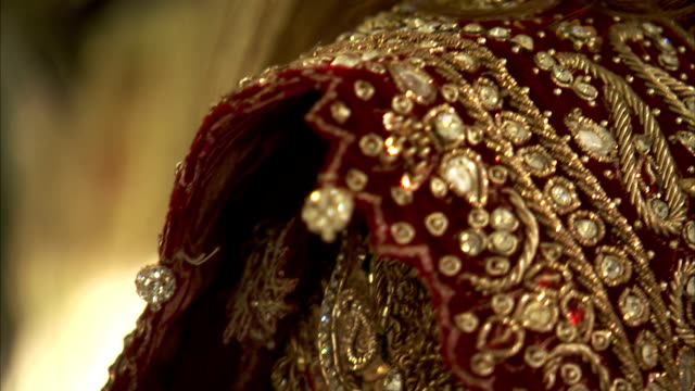 ornate embroidery and beading decorate a dress. - gold dress stock videos & royalty-free footage