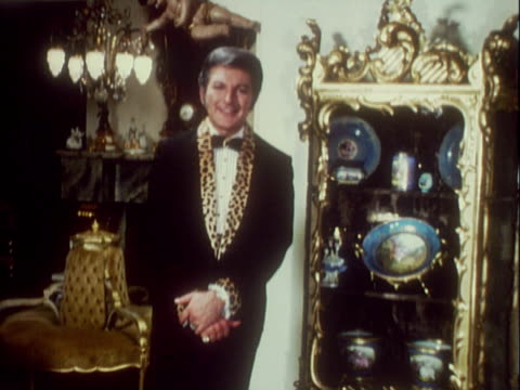 vidéos et rushes de ornate gold porcelain statue of 18th century woman / spinning la cu golden chandelier / ms musician liberace wearing black tuxedo with leopard print... - ornement