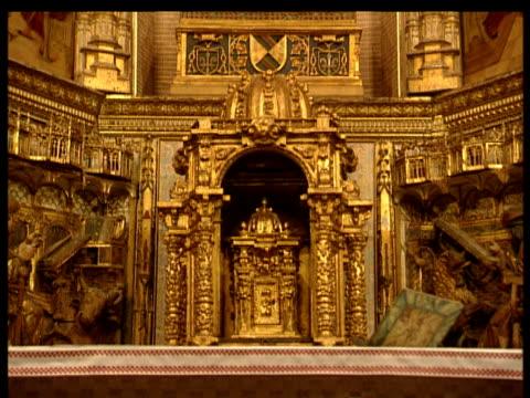 stockvideo's en b-roll-footage met ornate golden altar in church in santillana spain tilt up past paintings and relief sculptures including crucifixion - altaar