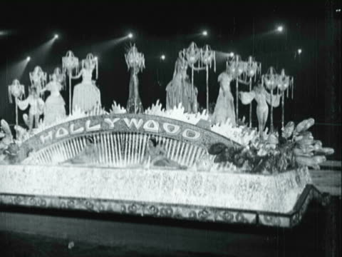 MONTAGE Ornate Hollywood parade floats, includes displays of evening gown clad women atop float standing beside stand based chandeliers, Warner Brothers float and float depicting Cleopatra's ship / Los Angeles, California, United States