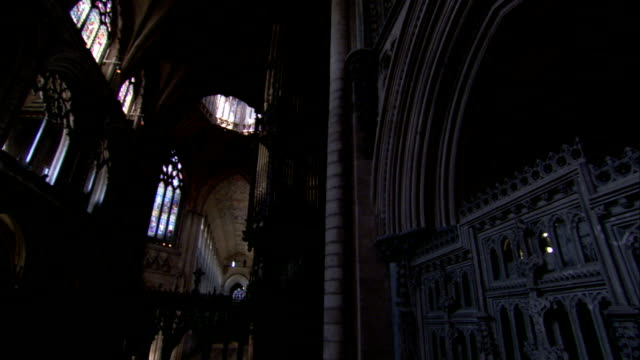 Ornate stained glass, arches, and latticework fill the interior of Ely Cathedral. Available in HD.