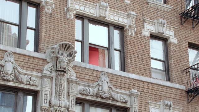 vidéos et rushes de ornate stone embellishments adorn the facade of an upscale brick apartment building in new york city. - façade