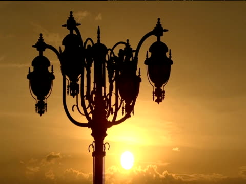 vídeos y material grabado en eventos de stock de ornate street light silhouetted in golden sunset bucharest - rumania