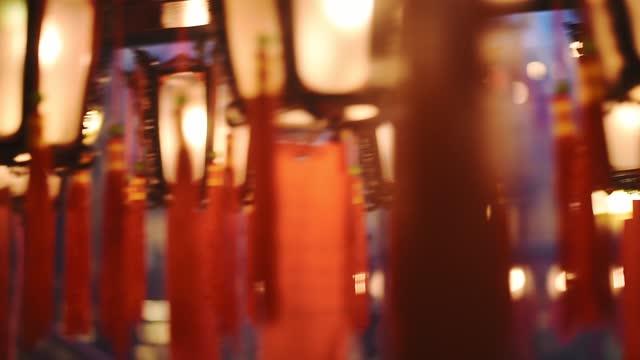 ornate traditional chineses lanterns hanging inside the man mo temple in hong kong - closeup panning shot - ハリウッドロード点の映像素材/bロール