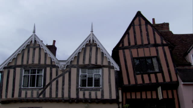ornate trim work decorates the roofline of a medieval house. available in hd. - lavenham stock-videos und b-roll-filmmaterial