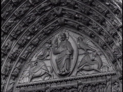 Ornately carved arch w/ Christian religious Icons Jesus Christ People dressed in coats hats walking out of ornate carved doorway church facade door...