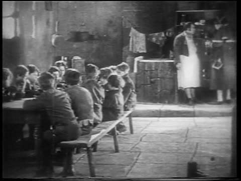 b/w 1922 orphan boy (jackie coogan) getting up from table + walking to men with bowl / feature - orphan stock videos & royalty-free footage