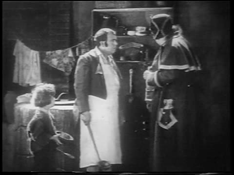 b/w 1922 orphan boy (jackie coogan) standing by two large men / feature - orphan stock videos & royalty-free footage