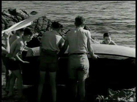 vídeos de stock, filmes e b-roll de boys' republic of italy orphan boys carrying wooden boat along tyrrhenian sea shoreline putting boat into water boys w/ long horn cattle strapped to... - animal de trabalho
