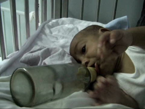 vídeos y material grabado en eventos de stock de poor conditions exposed baby lying on its side in a cot feeding from a bottle unattended - orfanato