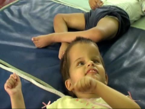 vídeos y material grabado en eventos de stock de poor conditions exposed two orphan children as one laughs and shakes his hands sot side view of rogers tilt down special needs child lying on a... - orfanato