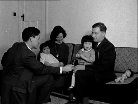 orphaned chinese children adopted by british families; england: kent: bromley: int cms man & baby with doll; group: zoom to father - mr mosley, what... - beautiful people stock videos & royalty-free footage