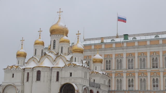 orthodox church under the snow at the kremlin, russian flag - moskau stock-videos und b-roll-filmmaterial