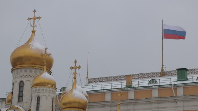 orthodox church under the snow at the Kremlin, Russian flag