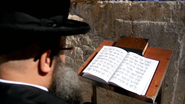 orthodox jew praying at western wall in old city, over the shoulder view, close-up / jerusalem old city - western script stock-videos und b-roll-filmmaterial
