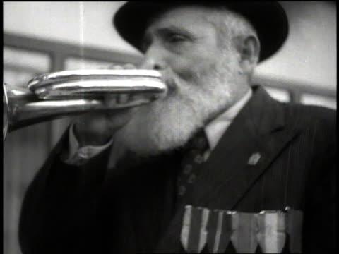 Orthodox Jewish man wearing medals blows Shofar horn to announce the start of Sabbath / Tel Aviv Israel