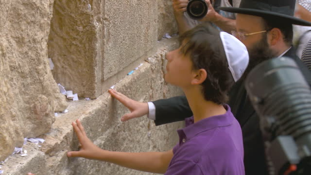 stockvideo's en b-roll-footage met cu zo ms orthodox jews praying at wailing wall, being filmed / jerusalem, israel - oude stad
