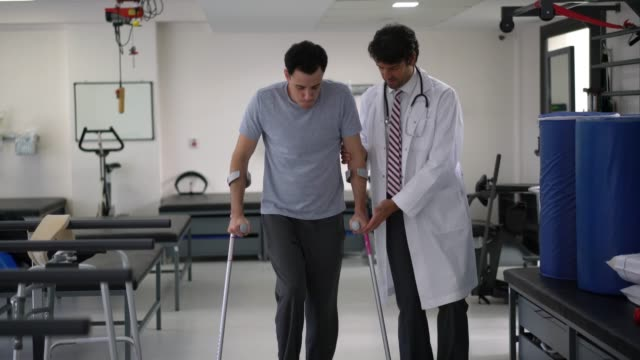 Orthopedist at the hospital helping a young patient use crutches for the first time