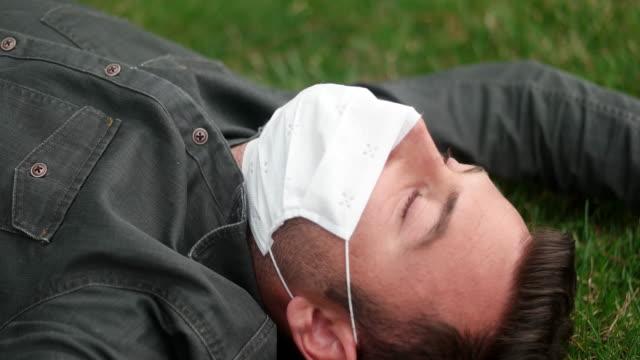 vídeos y material grabado en eventos de stock de o rasgo de un enfermo usando máscara médica en un bacground del parque público de la ciudad. - sentado