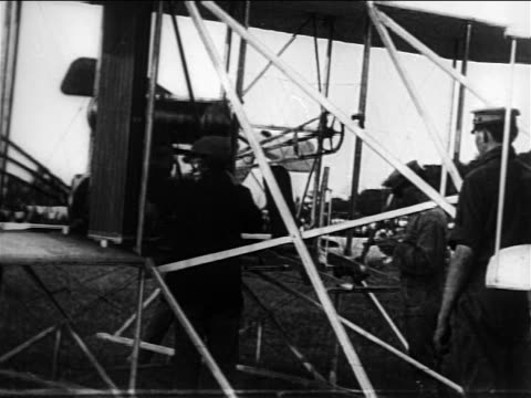 Orville Wright starting propeller of early airplane / documentary
