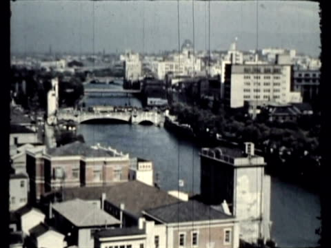 vídeos de stock, filmes e b-roll de ws ms pan osaka castle, japanese cityscape with multiple bridges spanning river, shopping street with large modern signage / osaka, japan / audio - 1951