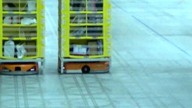 osaka prefecture--an army of amazon japan robot discs briskly hauled tall shelves stacked with items across the firm's warehouse floor here on april... - distribution warehouse stock-videos und b-roll-filmmaterial