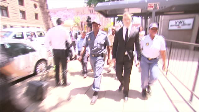 oscar pistorius back in court to continue sentencing hearing shows exterior shots oscar pistorius arriving at court and helping cameraman to his feet... - ピストリウス恋人射殺事件点の映像素材/bロール