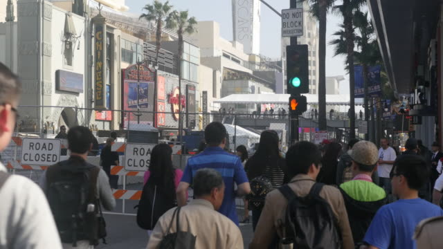 stockvideo's en b-roll-footage met oscar preparation is underway, it draws tourists to hollywood boulevard, hollywood sign, and the hollywood walk of fame. asian reporter is doing the... - boulevard