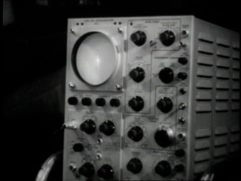 1950 montage oscilloscope reading voltage from medical device / new york city, new york, united states - オシロスコープ点の映像素材/bロール