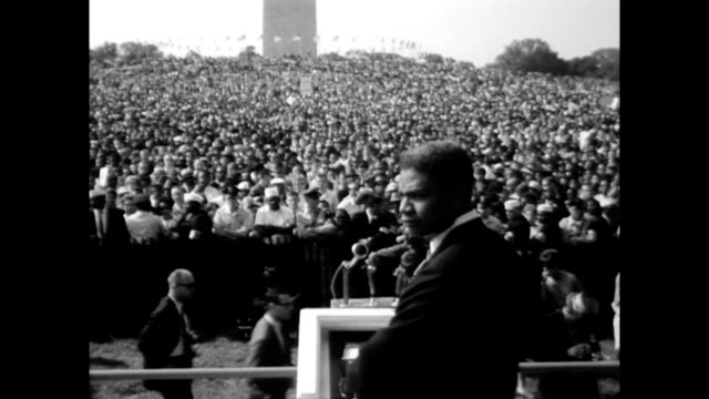 vídeos de stock e filmes b-roll de / ossie davis on stage asking people to start moving as the march begins / people holding placards as they start to mobilize actor ossie davis... - 1963