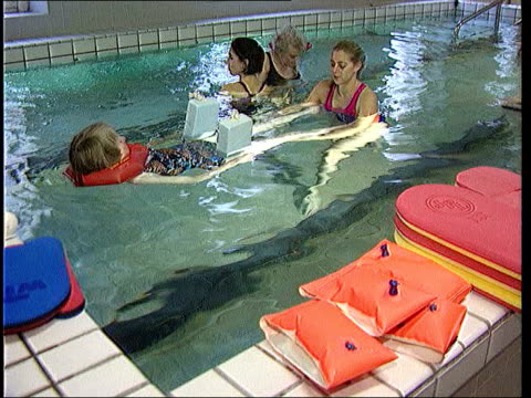 new treatment on sale; lib bath: patients undergoing physiotherapy treatment in swimming pool - osteoporosis stock videos & royalty-free footage