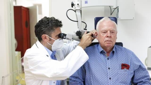 otolaryngologist undersöker örat av en äldre man - öra bildbanksvideor och videomaterial från bakom kulisserna