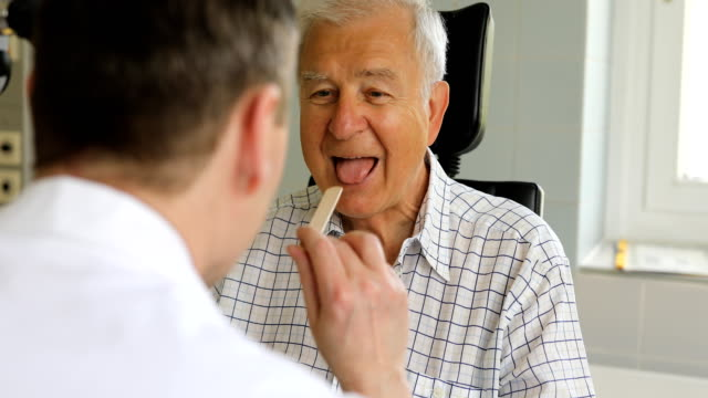 otolaryngologist examining senior patient's throat - clinic stock videos & royalty-free footage